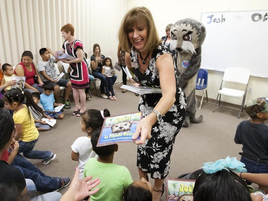 """Susan Acuna, president/CEO of Literacy Council Gulf Coast, passes out """"Josh the Otter"""" books at the Literacy Council Gulf Coast center in Bonita Springs."""