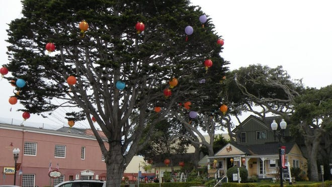Linda Lange/Special to the News Sentinel Lanterns hang on trees in Pacific Grove as the city prepares for the Feast of Lanterns, a celebration of its history and culture. A promenade along the Pacific Coast has many historical homes.