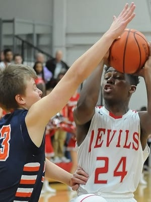 Senior Raider guard Tyler Howat blocks West Side's all-time leading scorer Nai Carlisle Saturday night. Howat's 10 points added to a Harrison victory over the Red Devils.