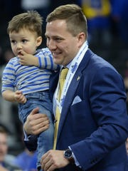 South Dakota State coach T.J. Otzelberger carries his son, Jayce, to a news conference after his team won the Summit League tournament last season.