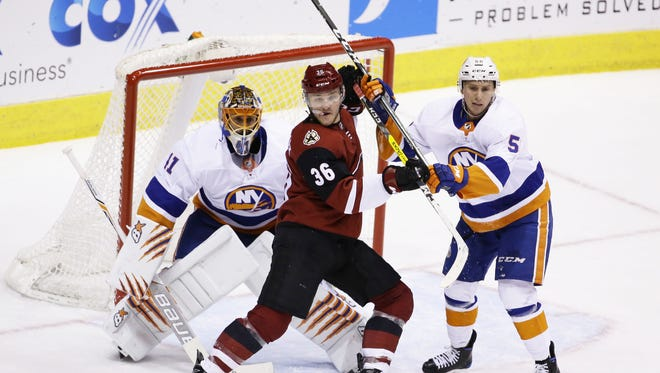 Arizona Coyotes' Christian Fischer battles for position with New York Islanders Tanner Fritz in the 2nd period on Jan. 22, 2018 at Gila River Arena in Glendale, Ariz.