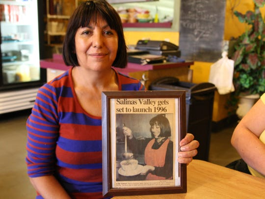 "Marina Espinoza sits at her restaurant ""Mama Lupita's"" on Salinas Street holding an article of her serving up a bowl of pozole."