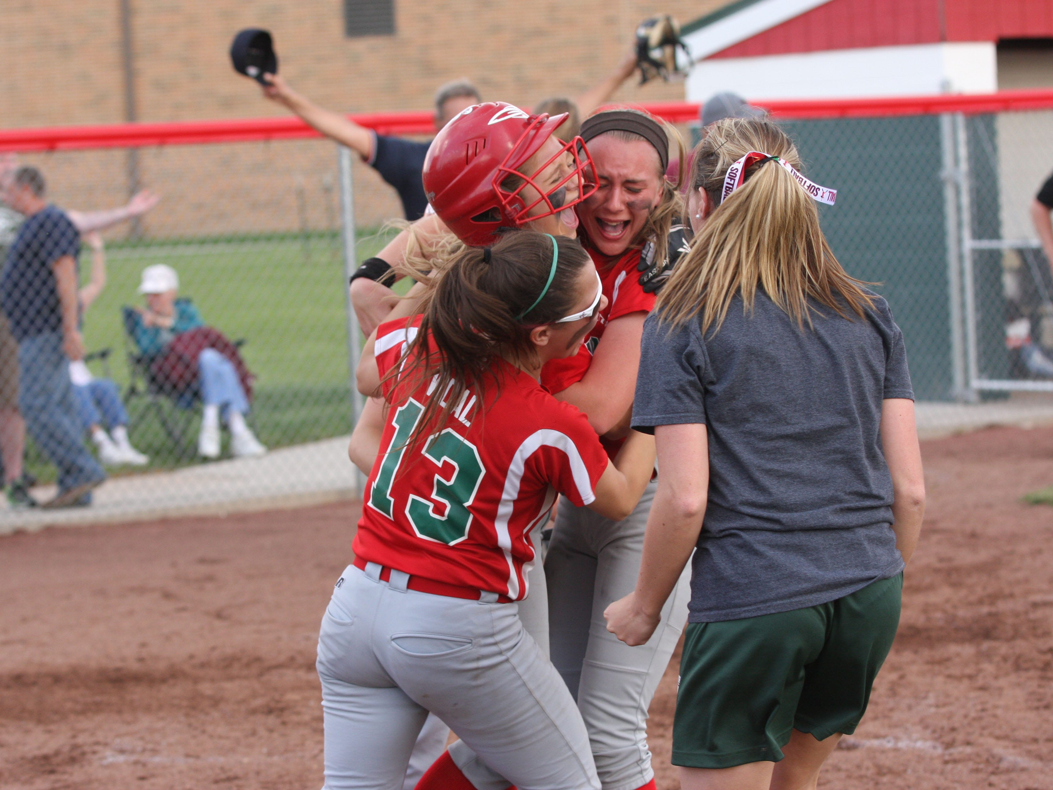 Oak Harbor's Seree Petersen (wearing helmet) is greeted by her teammates after scoring the game-tying run on a close play at the plate. The Rockets defeated Willard 2-1 in 12 innings in the sectional tournament at Oak Harbor.