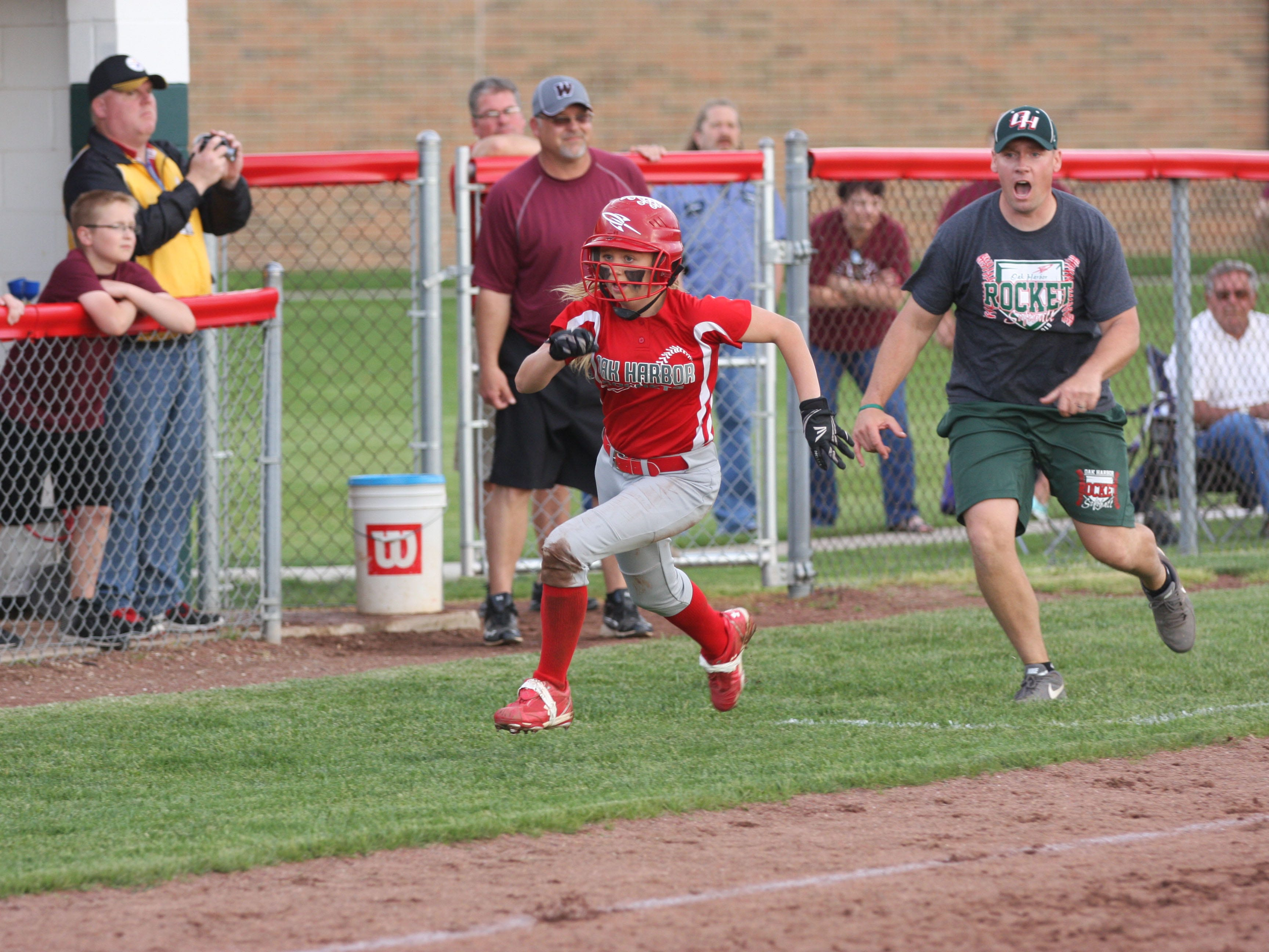 Coach Chris Rawski sends Seree Petersen home to score the game-tying run in the 11th inning Friday. The Rockets defeated Willard 2-1 in 12 innings in the sectional tournament at Oak Harbor.