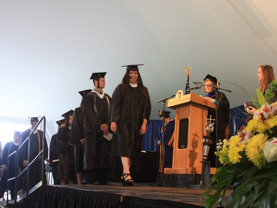 One of 583 graduates, Maria Lopez, steps across the stage to receive her diploma at Mount Saint Mary College Saturday in Newburgh. Handing out the sheepskins was Professor Amanda Maynard.