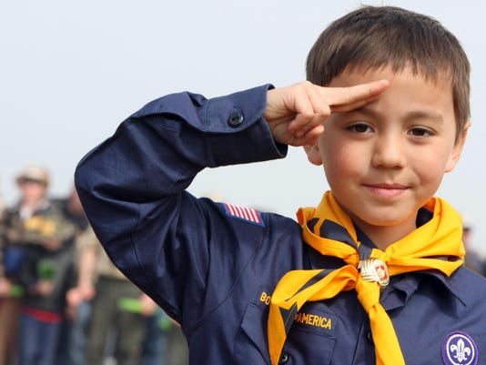 A US boy scout salutes while listening t