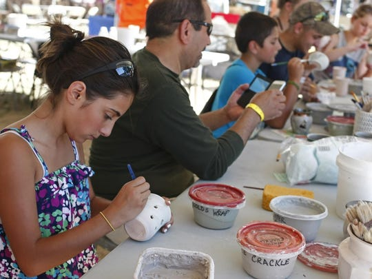 Hinani DeLima of Sandy glazed a clay pot with her family in the Artisans' Village at last year's Oregon State Fair. This year, the Artisans' Village will be located in the new Carts & Arts District.