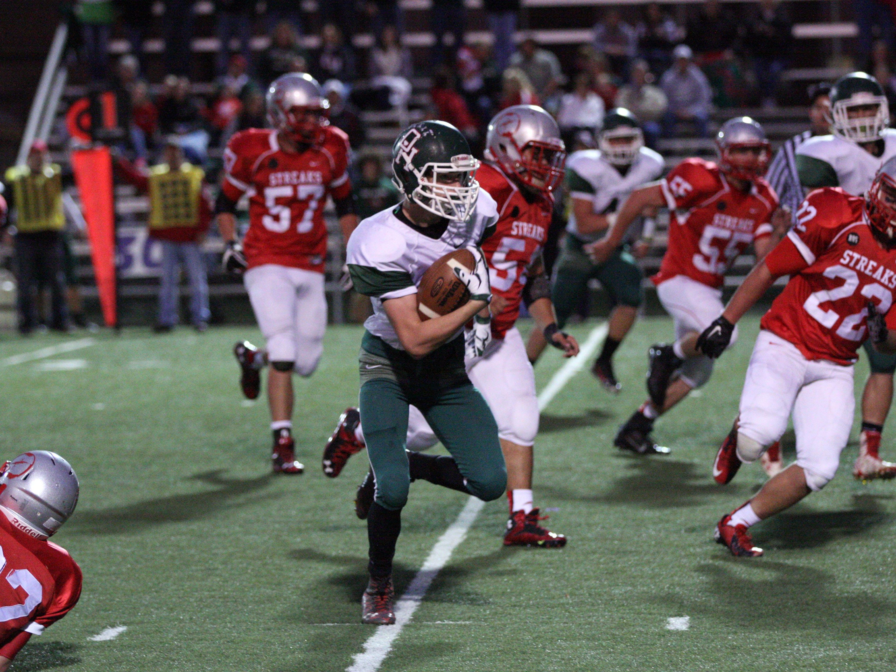 Oak Harbor's Dylan Mansor rushes for yardage against Fremont St.Joesph Central Catholic's defense. Photo by Doug Hise.
