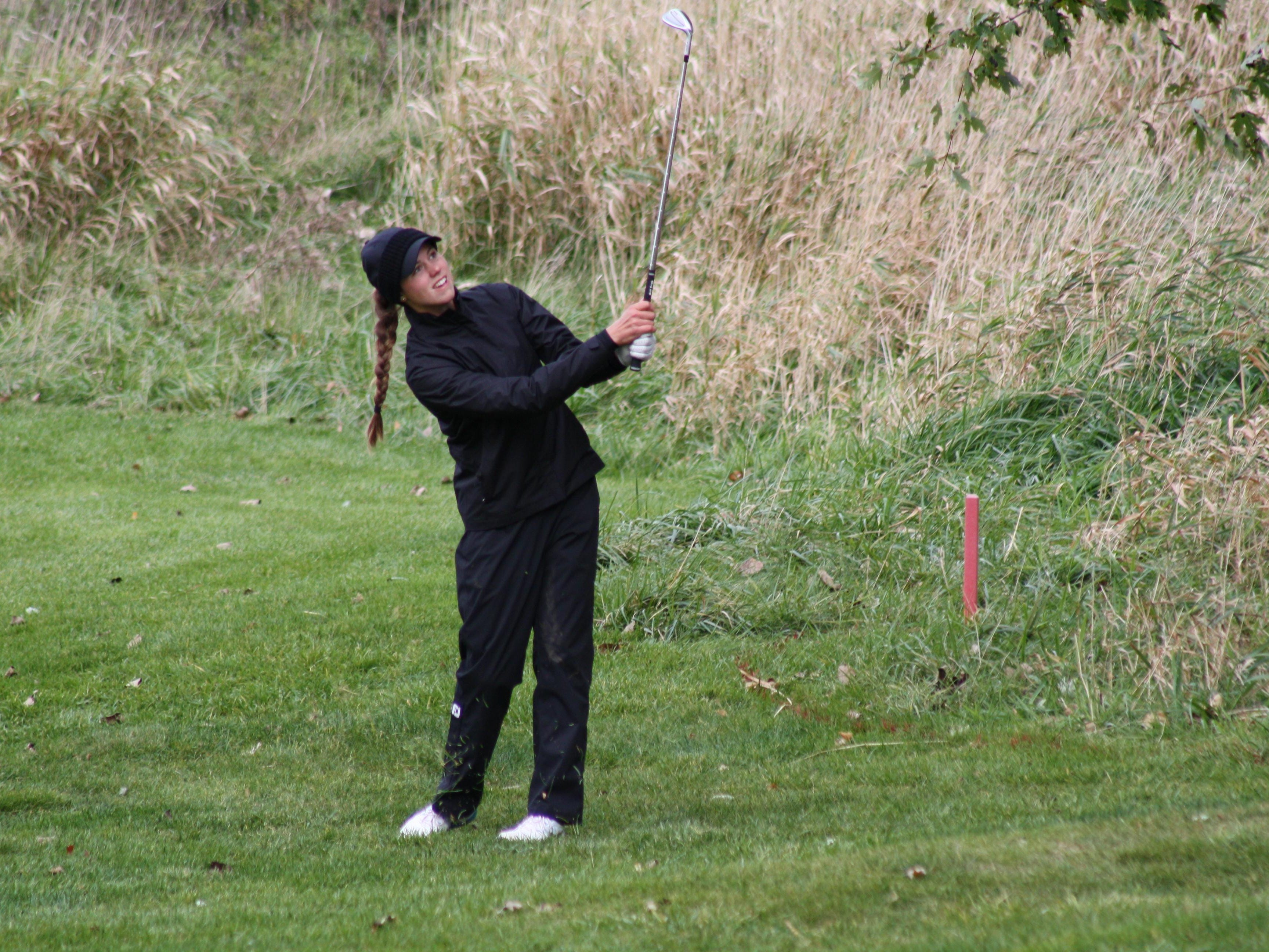 Brighton's Julia Dean hits an approach shot on No. 9 Saturday at Grand Valley's The Meadows. Dean shot 73 to win the individual title by one stroke.