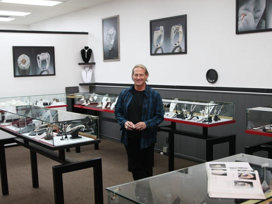 Jeff Appling stand in one of the show rooms he designed with posters of his original jewelry on the walls and samples in the cases