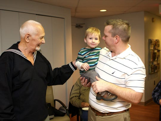 Chet Johnson, who tried on his new uniform following Wednesday's meeting, talks with his neighbors Chuck Walker and son Jack. Walker organized efforts to get Johnson a set of World War II-era navy blues.