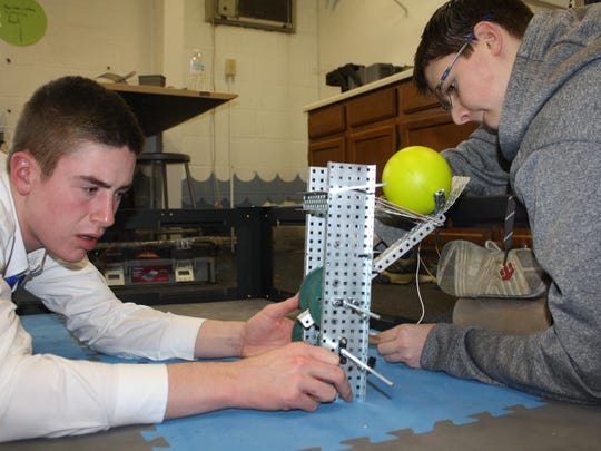 Covington Catholic High School junior Logan Franxman, of Crestview Hills, and sophomore Brett Shomaker, of Crescent Springs, adjust a ball catapult design for a robot they are creating in after school robotics club.