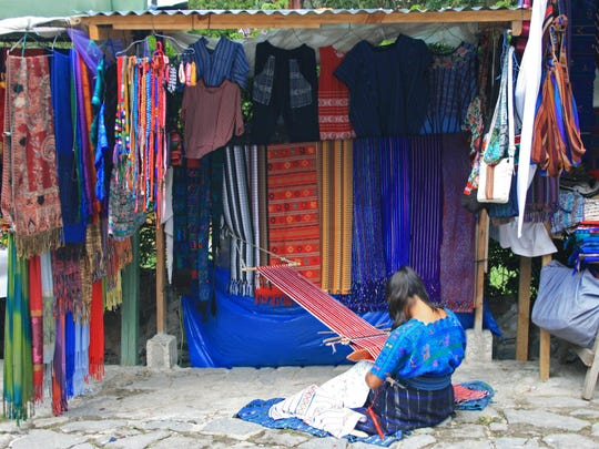 A woman uses a weaving loom in Santa Catarina Palopo, Guatemala.
