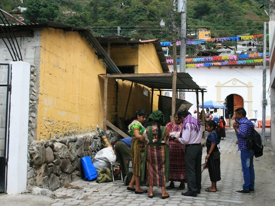 Mayan women in traditional dress converse with men in Santa Catarina Palopo, Guatemala.