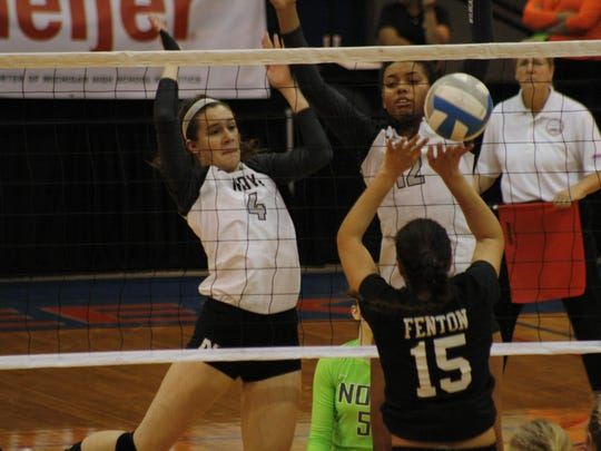 Novi's Emmy Robinson, left, and Abryanna Cannon battle at the net with Fenton's Delaney Miesch during Novi's semifinal win Friday.