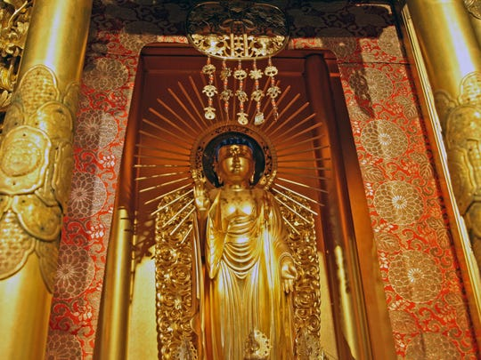 The gold statue of a standing Buddha in the sanctuary