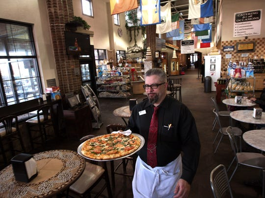 Waiter Joseph Mongioi of Bloomfield delivers a pizza at Calandra's.