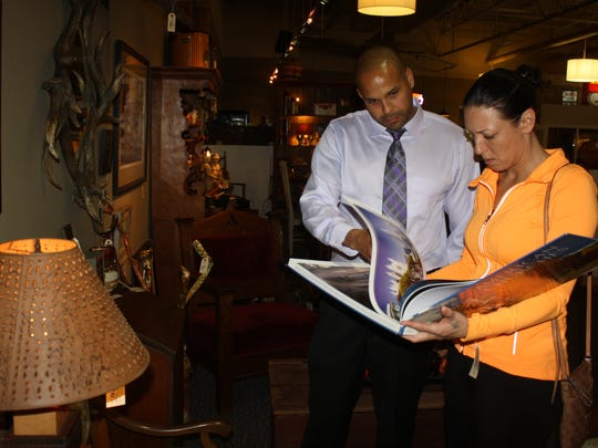 Downtown Cincinnati residents Michael Ferguson and Melissa Collins flip through a coffee table book in an aisle of furniture at Fort Thomas Antiques & Design.
