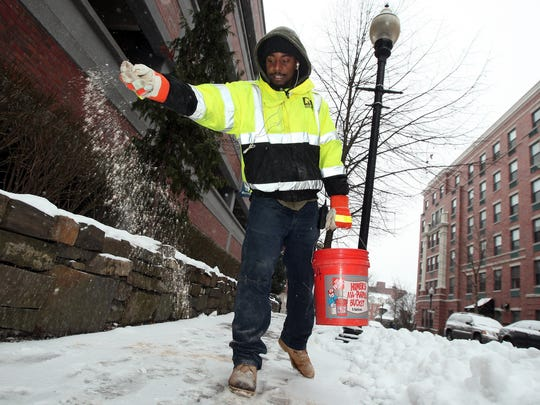 Shaun Dowman of the Morristown Parking Authority spreads salt on Cattano Avenue in anticipation of the impending blizzard.