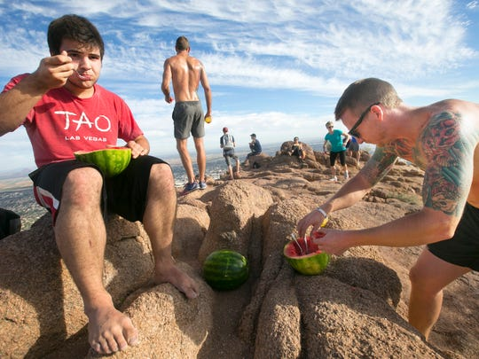 Jamie Trufin, 17, (left) of Phoenix, eats a watermelon as Devin Corbett of West Palm Beach, Fla., helps himself to some watermelon at the summit of Camelback Mountain from the Echo Canyon trail in Phoenix on Wednesday, November 19, 2014. For nearly the past six months Trufin has been hiking to the top of Camelback Mountain carrying watermelon and sharing it with other hikers on the summit.