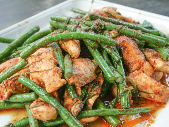 Pad Prig King, made with yard-long beans, pork, red curry and thinly sliced kaffir lime leaves, is a common dish in Thailand.