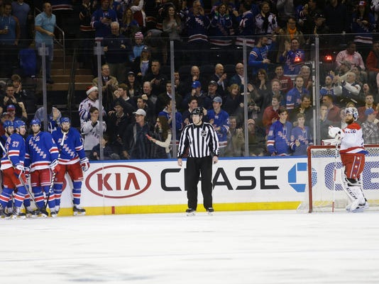 The New York Rangers celebrate a goal by Rick Nash, left, as Washington Capitals goalie Braden Holtby, right, looks away during the first period of an NHL hockey game Tuesday, Dec. 23, 2014, in New York.  (AP Photo/Frank Franklin II)