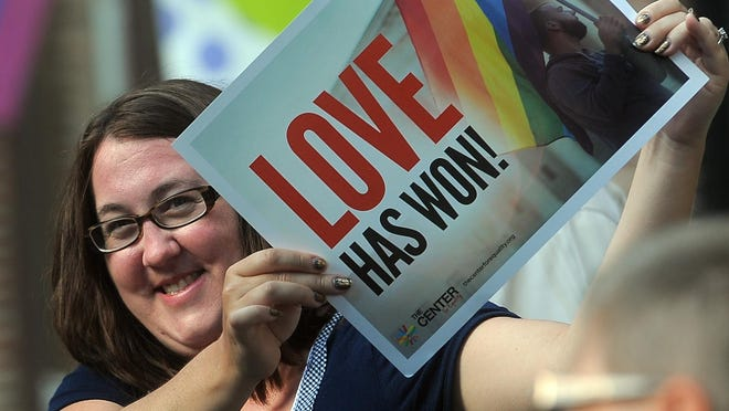 Melina Raff holds a sign outside of Lucky's in downtown Sioux Falls during a celebration in honor of the Supreme Court's decision for marriage equality in all 50 states on Friday, June 26, 2015.