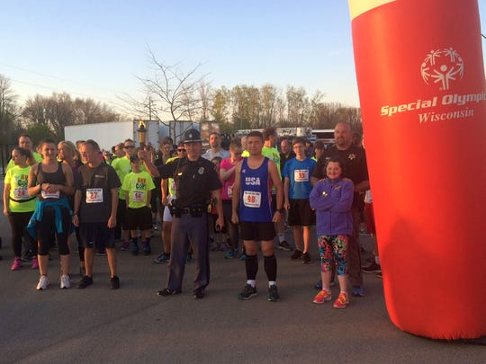 Trooper Andy Jacobs, middle, from the Wisconsin State Patrol carries a torch at the start of the Run with the Cops 5K Run/Walk to support local Special Olympics Wisconsin athletes outside St. Norbert College's Donald J. Schneider Stadium in De Pere on Thursday night, May 5, 2016. Two-time Special Olympics World Games gold medalist Alex Guild of Lawrence was the top finisher in Thursday's event.