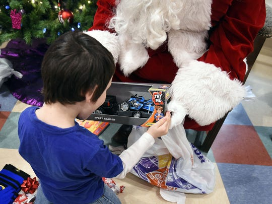 Santa helps a young boy open a present Tuesday at Serenity.