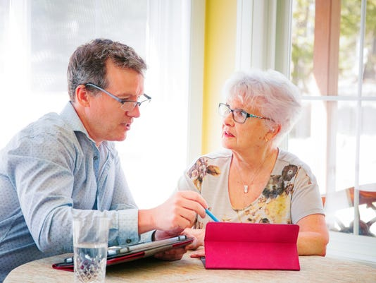 Senior woman asks for guidance with tablet from her grown up son