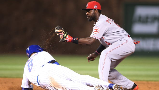Cubs left fielder Chris Coghlan is tagged out by Reds second baseman Brandon Phillips during the  third inning Monday at Wrigley Field.