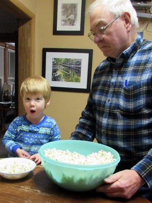 Grandpa Bob shares a bowl of popcorn with grandson Harrison during a recent visit.