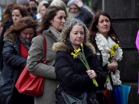 Former classmates of Dolores O'Riordan carry yellow
