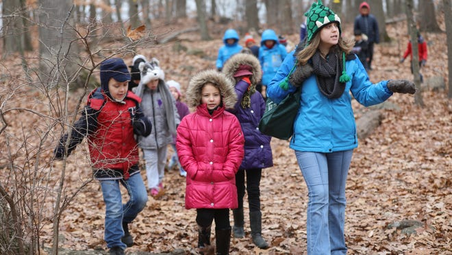 Environmental educator Jen Lodico explains what the markers on a tree mean during a hike on Monday. The Tenafly Nature Center is home to a winter camp for youngsters this week, where they will play games while learning about the environment.