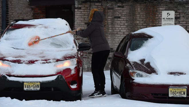 A woman clearing her car of snow and ice Wednesday morning after the blizzard in East Rutherford.