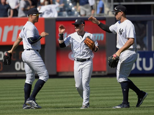 New York Yankees left fielder Giancarlo Stanton, left, center fielder Clint Frazier and right fielder Aaron Judge, right, celebrate after the Yankees defeated the Seattle Mariners 4-3 in a baseball game Thursday, June 21, 2018, at Yankee Stadium in New York. (AP Photo/Bill Kostroun)