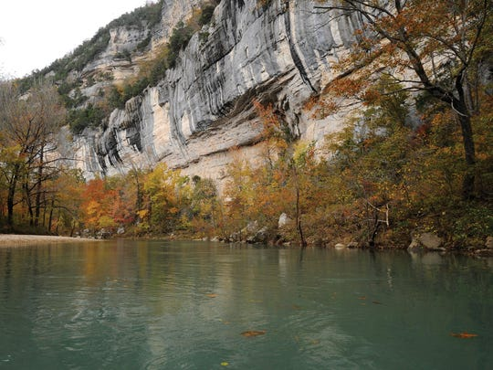 A lazy stretch of the Buffalo River flows beneath towering limestone bluffs.