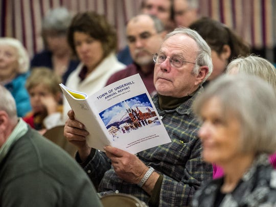 John LaRue follows along with the town report during during town meeting in Underhill on Tuesday, March 3, 2015.