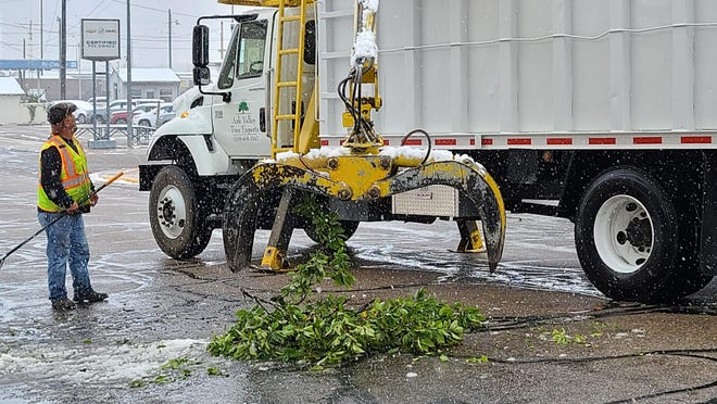 Gilbert Leyba with the La Junta streets department works with his crew to clear north Raton Ave. of downed tree branches Wednesday morning.