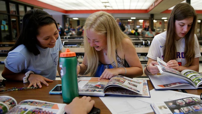 Ariana Juarez, Dylan Roesken, and Shelby Hiltgen, all sophomores at Appleton West High School, look through their yearbooks .