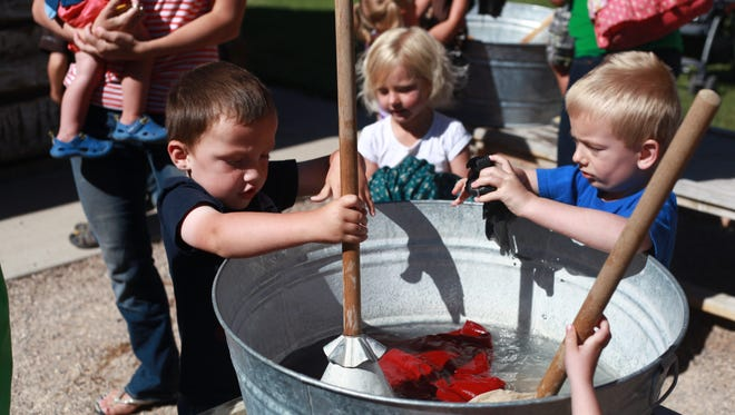 Several kids mix up the clothes provided for children during reading time at the Frontier Homestead Museum on Tuesday June 17, 2014. This activity was a lesson in how they washed clothes during the time of the early settlers.