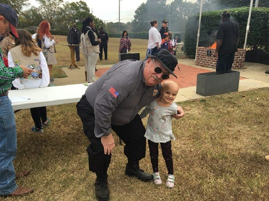 Geoff Colt, a Vietnam veteran and member of VVA's chapter 607 hugs Lilly during the Central Alabama chapter's annual  Veteran's Day flag retirement ceremony.