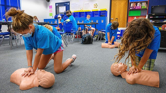 Middle school students taking part in the St. Johns County School District's marine science camp practice CPR on dummies in a classroom at Gamble Rogers Middle School in St. Augustine on Thursday.