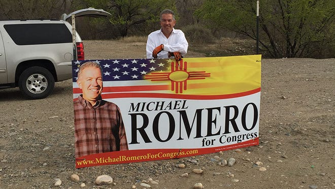 Michael Romero stands behind a campaign sign. Romero is running for New Mexico's District 3 seat in the U.S. House of Representatives.