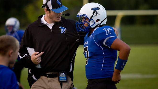 Cros-Lex coach Garrett Grundman talks with Justin Johnston during a football game.