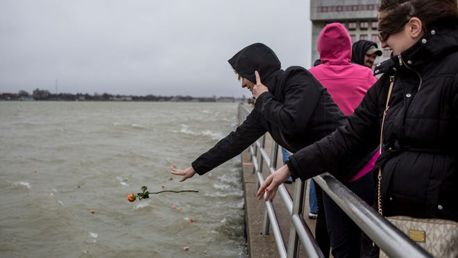 Brianna Monzo, an assistant prosecuting attorney with the county, tosses a flower into the St. Clair River during a ceremonial flower toss in honor of National Crime Victims' Rights Week Thursday, April 6, 2017 at Kiefer Park in Port Huron.