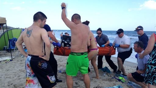 Emergency responders assist a teenage girl at the scene of a shark attack in Oak Island earlier this month. Officials say a 17-year-old boy is the latest victim of a shark attack off North Carolina's coast on Saturday, the second attack in as many days and the sixth attack in the past two weeks.