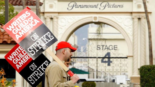 FILE - In this Jan. 23, 2008 file photo, striking film and television writers picket outside Paramount Studios in Los Angeles. Hollywood is facing a cliffhanger after members of the Writers Guild of America voted overwhelmingly to authorize a strike that could begin as soon as May 2, the day after the current contract ends. The previous writers' strike lasted 100 days in 2007-08 and was costly to the businesses that serve Hollywood and to consumers expecting to be entertained.