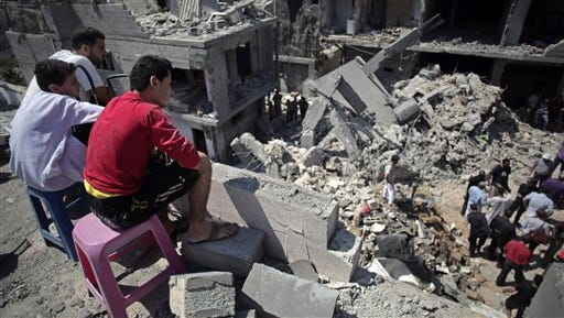Palestinians search in the rubble of a destroyed house where eight members of the Al Haj family were killed in a strike early morning in Khan Younis refugee camp, southern Gaza Strip on Thursday, July 10, 2014. Israel dramatically escalated its aerial assault in Gaza Thursday hitting hundreds of Hamas targets, as Palestinians reported more than a dozen of people killed in strikes that hit a home and a beachside cafe and Israel's missile defense system once again intercepted rockets fired by militants at the country's heartland. (AP Photo/Khalil Hamra)