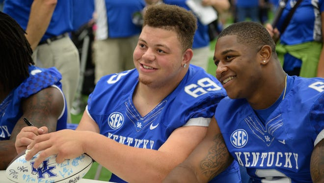 Defensive tackle Matt Elam and defensive end Jason Hatcher pose for a picture during the University of Kentucky football fan day at the UK Nutter Training Center in Lexington, KY. Saturday, August 9, 2014.